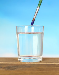 Brush with color paint in glass of water,