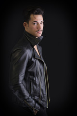 Attractive young man with leather jacket, on dark background