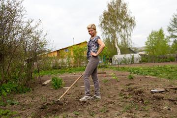 Shapely blond leveled ground rake in the spring garden
