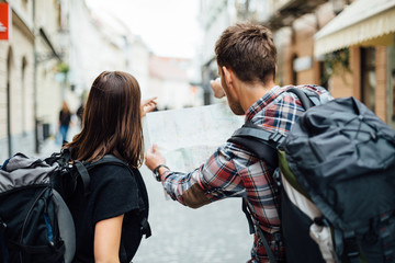 Couple of backpackers looking at city map Wall mural