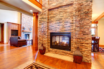 Luxury house interior. Stone wall with fireplace