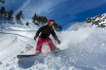 Woman snowboarder in motion in mountains Wall mural