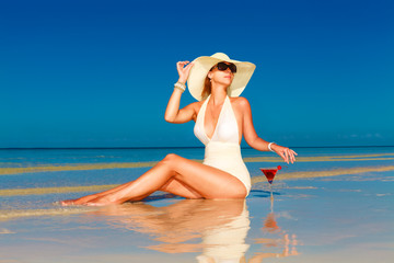 young woman in straw hat sitting at the tropical beach and enjoy