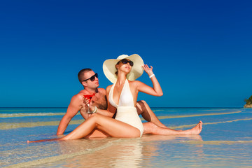 young couple in love at the tropical beach and enjoying cocktail