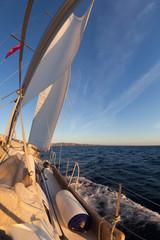 Sailboat during the regatta at sunset ocean