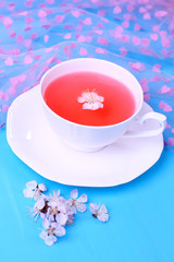 Fragrant tea with flowers on wooden table close-up