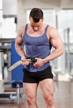 Man fastening belt in the gym