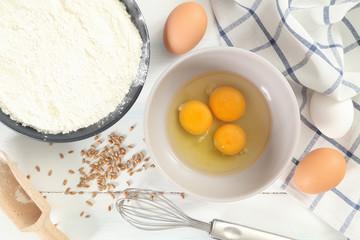 uova con farina su tavolo bianco
