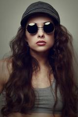 Closeup fashion woman portrait in glasses and cap. Vintage style