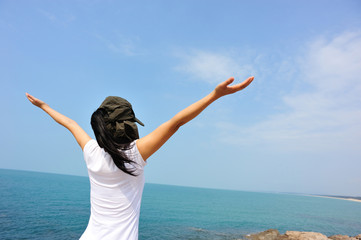cheering woman open arms at seaside rock looking at the view