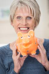 lachende seniorin hält sparschwein fest