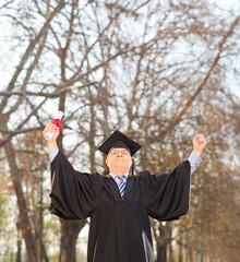 Happy mature graduate holding diploma outdoors