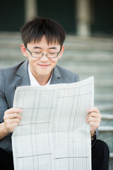 A young businessman reading newspaper