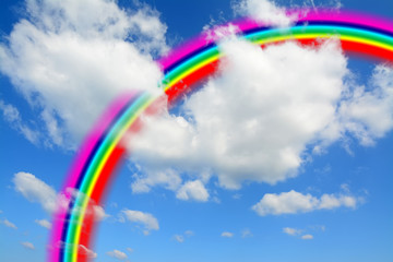 white clouds and blue sky with a colorful rainbow