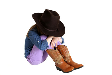 Cowgirl sitting sulking with head down on her knees