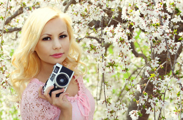 Blonde Girl with Retro Camera over Cherry Blossom. Beautiful