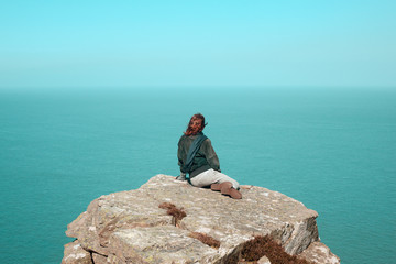 Young woman sitting on cliff by the sea