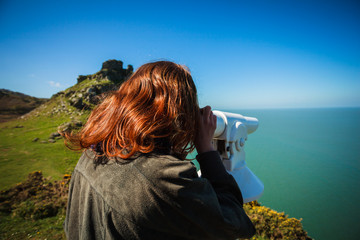 Woman looking through telescope by the sea