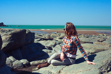 Young woman sitting on a rocky beach