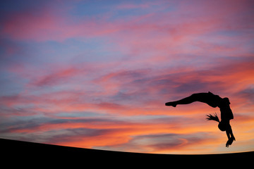 Wall Mural - silhouetted gymnast doing a back handspring in sunset sky