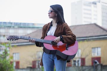 Girl playing guitar in urban scene