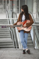 Girl standing and playing guitar