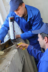 Two men in working clothes used mounting foam