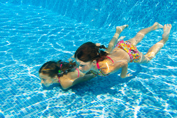 Happy kids swim underwater in pool and having fun