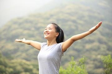 cheering hiking woman enjoy the beautiful view at mountain peak