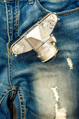 Close-up detail of vintage jeans with classic camera