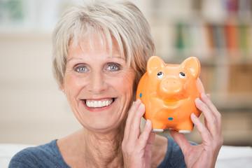 lächelnde seniorin hält oranges sparschwein