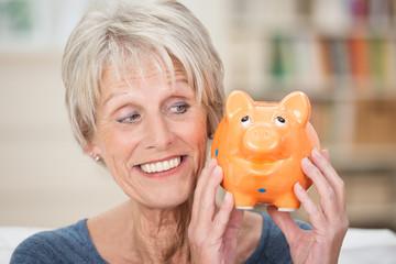 lächelnde ältere frau schaut auf sparschwein