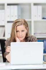 geschäftsfrau schaut besorgt auf laptop