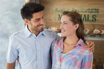 Couple with arm around at bakery