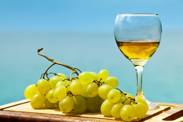 White grape and glass of wine placed on wooden plate