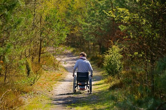 Disabled woman riding a wheelchair in the woods