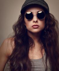 Sexy cool female model in sun glasses. Vintage portrait