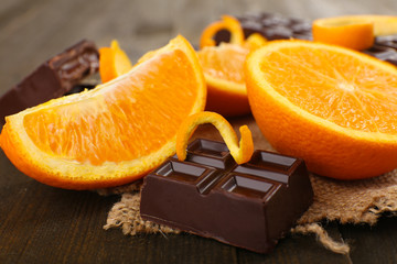 Fototapete - Chocolate and orange on wooden table