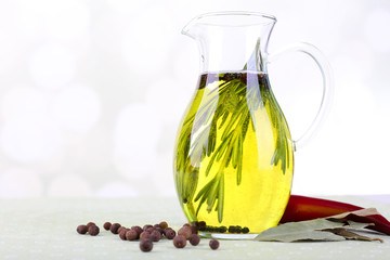 Essential Oil with rosemary in glass jug, isolated on white
