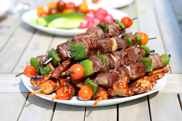 Assorted delicious grilled meat with vegetableы on white plate