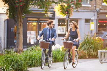 Businesswoman And Businessman Riding Bike Through City Park Fototapete