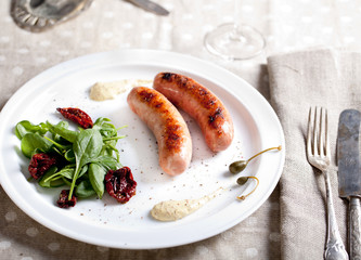 Grilled sausages with salad on a white plate