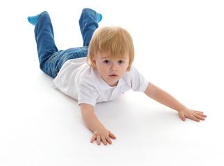 Portrait of a cute little boy lying on floor