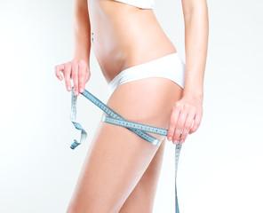 Slim girl with centimeter measuring her slim beautiful body.