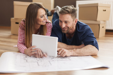 Couple arranging new apartment with digital tablet