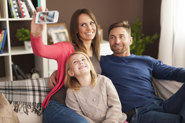 Happy family taking selfie at home