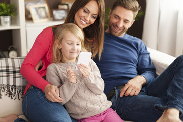 Cute little girl with parents playing by mobile phone at home