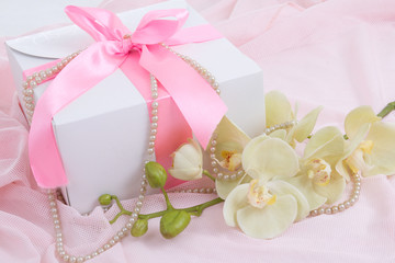 gift box with pink ribbon, orchid and pearl necklace