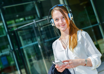 pretty worker listening to music in front her company