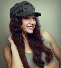 Happy smiling girl in fashion cap. Woman with curly hair